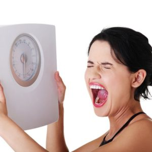 frustrated-woman-with-a-scale-min